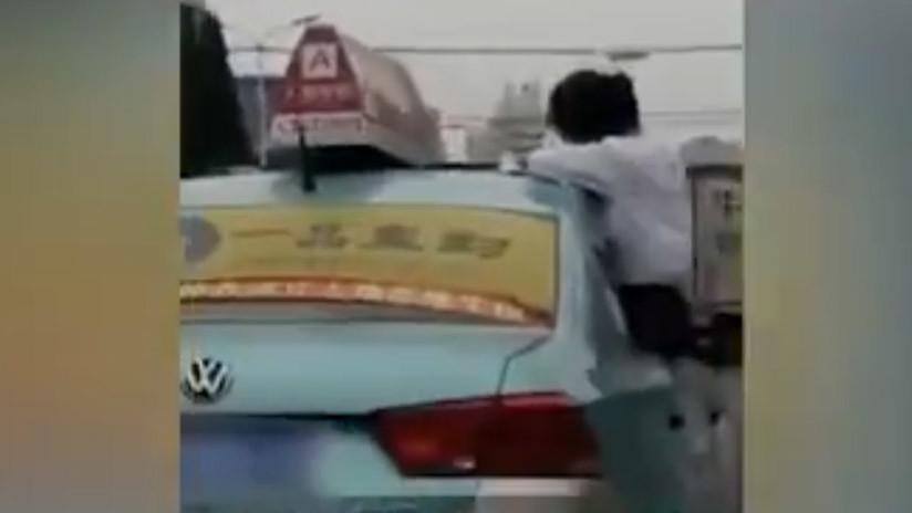 VIDEO: Una estudiante hace su tarea en el techo de un taxi en movimiento en China