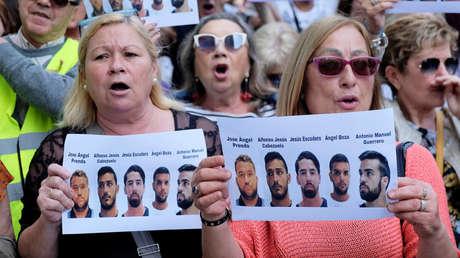 La gente sostiene carteles con retratos de los integrantes del grupo 'La Manada' en forma de protesta afuera de la Ciudad de la Justicia, en Valencia, España, el 27 de abril de 2018.