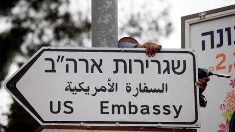 Un trabajador cuelga una señal de tráfico que dirige a la Embajada de EE.UU. en Jerusalén, el 7 de mayo de 2018.
