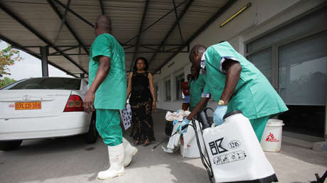 Sanitary worker prevents disinfection on a colleague in Kinshasa October 21, 2014