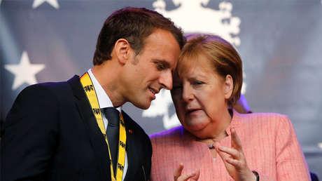 El presidente francés, Emmanuel Macron, habla con la canciller alemana, Angela Merkel, después de recibir el premio Carlomagno en Alemania, 10 de mayo de 2018