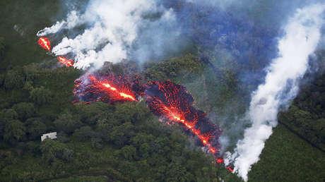 Lava estalla desde la fisura al este de Leilani Estates mientras las erupciones volcánicas actuales de Kilauea, Hawái, los EE.UU., el 13 de mayo, 2018