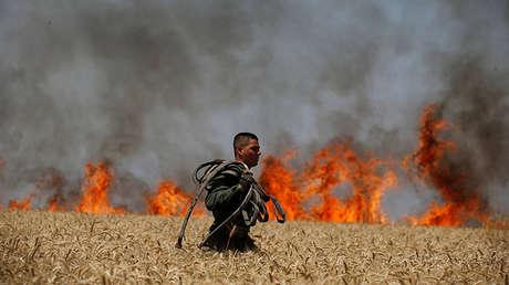 Soldado israelí porta una manguera mientras camina a través de un campo incendiado cerca de la frontera entre Israel y Gaza, el 14 de mayo de 2018.