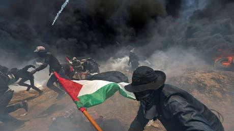 Palestinos huyen del fuego israelí durante una protesta en la frontera entre Israel y Gaza en el sur de la Franja de Gaza, el 14 de mayo de 2018.
