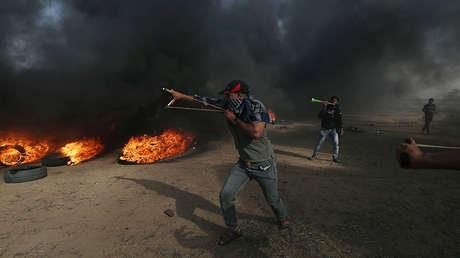 Un palestino usa una honda para arrojar piedras en la frontera de Israel y Gaza.18 de mayo de 2018.