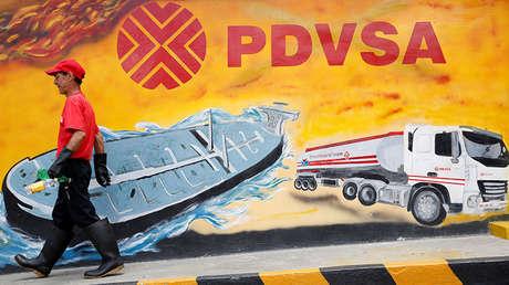 Trabajador petrolero camina delante de un mural alusivo a la empresa estatal.