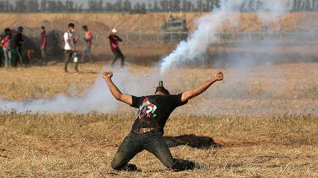 Un manifestante palestino sostiene un bote de gas lacrimógeno con la boca durante una protesta en Gaza, el 1 de junio de 2018.