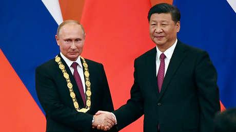 El presidente chino Xi Jinping felicita al presidente ruso Vladímir Putin tras otorgarle la medalla de la amistad en Pekín, 8 de junio de 2018.
