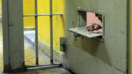 Un prisionero mira por una abertura en una cárcel de Magdalena, provincia de Buenos Aires (Argentina).