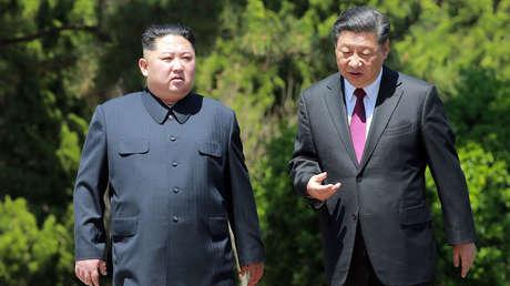 El presidente de China, Xi Jinping, y el líder norcoreano, Kim Jong-un, hablan durante un paseo en la ciudad de Dalián (China), el 8 de mayo de 2018