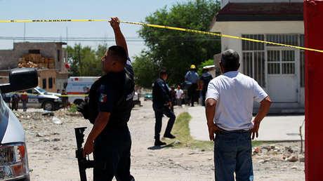 Un policía sostiene un cordón policial mientras un pariente reacciona al asesinato de varias personas en Ciudad Juárez, México, el 23 de junio de 2018.