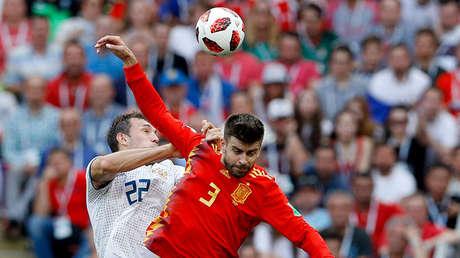 Gerard Piqué lucha por el balón con Artiom Dziuba en el partido España-Rusia en Moscú, el 1 de julio de 2018.