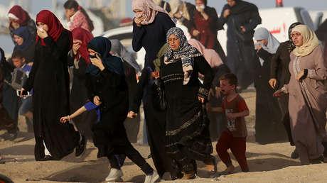 Manifestantes palestinas huyen de los gases lacrimógenos lanzados por las tropas israelíes durante una protesta en la Franja de Gaza, el 3 de julio de 2018.