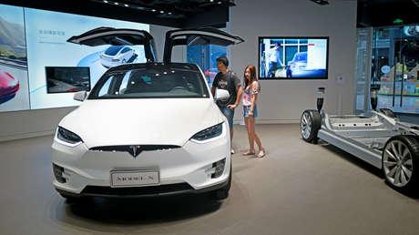 Gente visita una sala de exposición Tesla en Beijing, China, el 4 de julio de 2018.