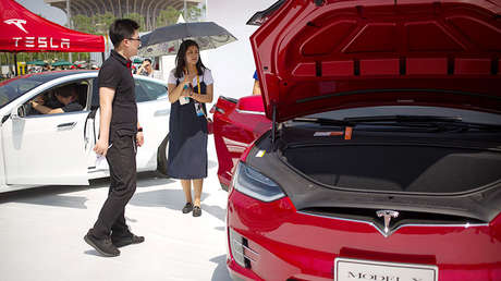 Visitantes de la Global Mobile Internet Conference en Pekín, junto a un coche Tesla Model X, el 29 de abril de 2017.