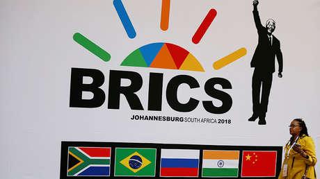 Una delegada pasa frente a un logotipo de los BRICS en Sandton (Sudáfrica), el 24 de julio de 2018.