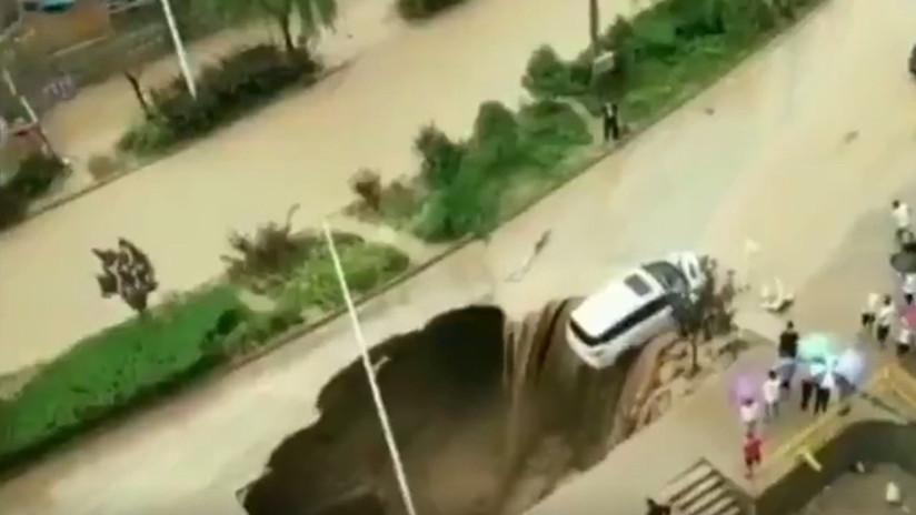 VIDEO: Las lluvias forman un agujero en una carretera y esta casi 'se traga' un coche