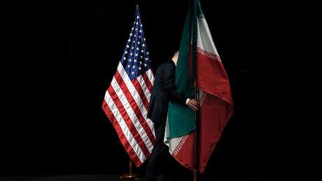 Un trabajador retira la bandera iraní tras una foto de grupo con representantes de EE.UU., Irán, China, Rusia, el Reino Unido, Alemania, Francia y la UE en Viena (Austria), el 14 de julio de 2015.
