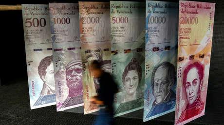 Un hombre pasa junto a pancartas que representan la moneda en el Banco Central de Venezuela (BCV), en Caracas, el 31 de enero de 2018.