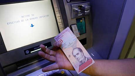 Un hombre muestra el nuevo billete de diez bolívares soberanos en un cajero automático en Caracas, el 20 de agosto de 2018.