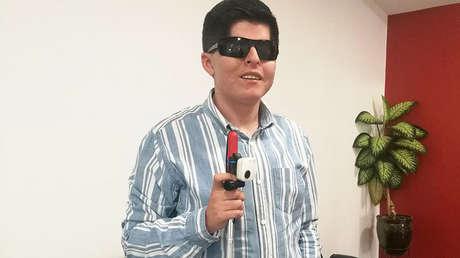 Kevin Freire usa un EyeClip en su bastón para ayudarse en su movilización, en Quito, agosto de 2018.