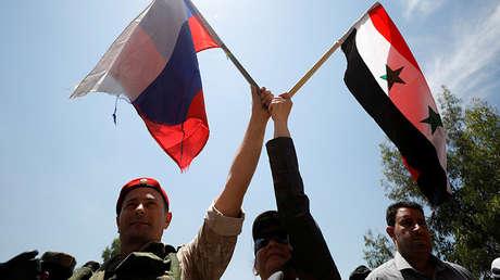 Un soldado ruso y una mujer siria agitan banderas durante la reapertura de la carretera entre Homs y Hama en Rastan, Siria, 6 de junio de 2018