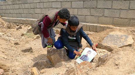 Dos menores con la foto de un niño que murió en el autobús que atacó la coalición liderada por Arabia Saudita, Saada, Yemen, 13 de agosto de 2018.