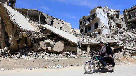 Dos sirios conducen una motocicleta frente a edificios dañados en Duma, en las afueras de Damasco, el 16 de abril de 2018.