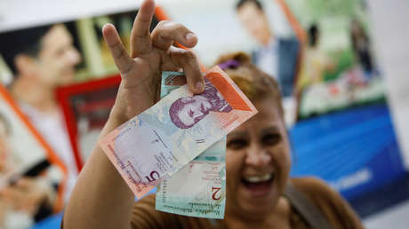Una mujer sonríe mientras muestra los nuevos billetes del Bolívar Soberano. 20 de agosto de 2018.
