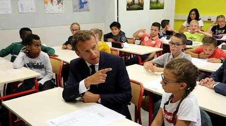 Macron junto a un alumno en una visita a una escuela secundaria en Laval, septiembre de 2018.