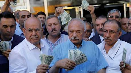 Hombres con dólares estadounidenses en sus manos frente a una oficina de cambio en Ankara, Turquía, el 14 de agosto de 2018