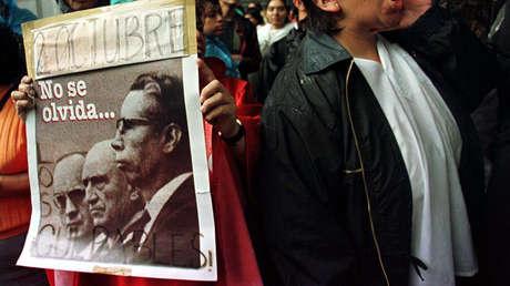 Una mujer protesta con una fotografía con expresidentes señalados por la matanza de Tlatelolco. Ciudad de México, 2 de octubre de 1998.