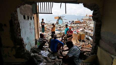 Unos residentes descansan cerca de una casa dañada por el tsunami, Wani, Célebes, 4 de octubre de 2018.