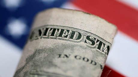 Un billete de dólar plegado frente a la bandera nacional de EE.UU.