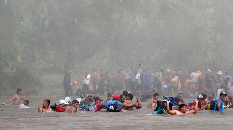 Parte de la caravana de migrantes cruza el río que divide Guatemala de México, el 29 de octubre de 2018.