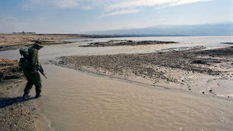 Soldado israelí camina en el agua en el punto donde el río Jordán y el Mar Muerto se encuentran.
