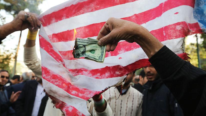 Manifestantes iraníes queman dólares y banderas de EE.UU. por la reanudación de las sanciones
