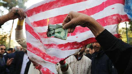 Manifestantes iraníes queman dólares para mostrar su rechazo a la política de Trump y a las sanciones de Washington, en Teherán, el 4 de noviembre de 2018.