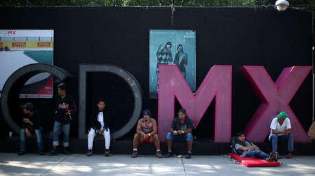 Migrantes descansan sobre un anuncio de promoción turística de Ciudad de México, el 7 de noviembre de 2018.