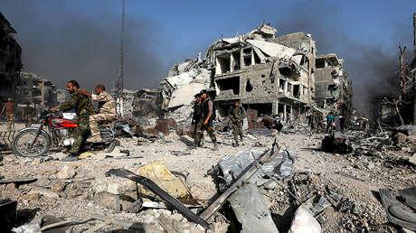Foto ilustrativa / Soldados del Ejército sirio circulan en moto entre escombros en al-Hajar al-Aswad (Siria), el 21 de mayo de 2018.