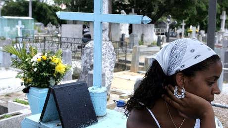 Una mujer se sienta en el cementerio cerca de la tumba de 'Ismael'. Caracas, 1 de octubre de 2004.