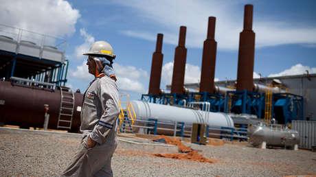Un trabajador petrolero pasa frente a una instalación operada por Pdvsa. 28 de julio de 2011.
