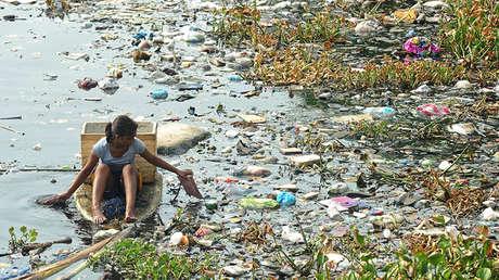 Niña navega por un río lleno de residuos en Navotas (Filipinas), el 6 de mayo de 2015.