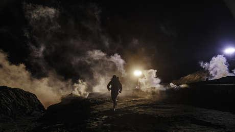 Migrantes corren tras haber cruzado desde Tijuana (México) hacia San Diego (EE.UU.), mientras agentes estadounidenses lanzan gas lacrimógeno al territorio mexicano a través de la valla fronteriza, el 1 de enero de 2019.