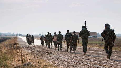 Combatientes kurdos de la milicia YPG caminan hacia Tel Abyad en Raqa, Siria, el 15 de junio de 2015.