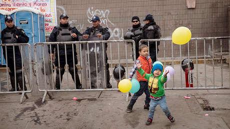 Niños juegan frente a la Policía Federal de México al exterior de una bodega vacía que es usada como refugio para los migrantes en el centro de Tijuana, México, el sábado 5 de enero de 2019.