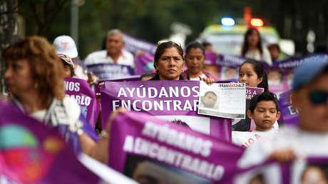 Personas con fotos de personas desaparecidas durante una marcha para conmemorar el Día de la Mujer en Xalapa, en el estado mexicano de Veracruz, el 10 de mayo de 2018.