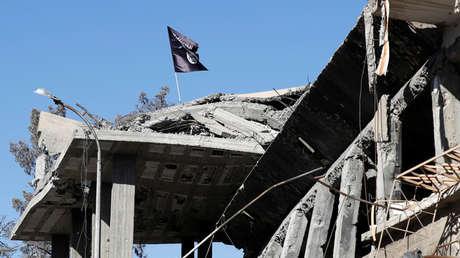 Bandera del Estado Islámico sobre una casa destruida en Al Raqa, Siria, 18 de octubre de 2017.