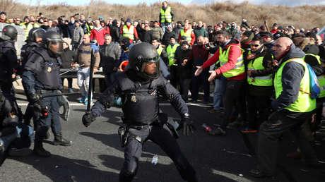 La policía se enfrenta a los taxistas en huelga que intentan bloquear una autopista en Madrid. 23 de enero de 2019.