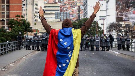 Hombre llevando bandera venezolana ante los policías en Caracas, el 23 de enero de 2019.